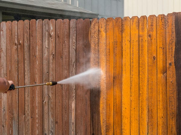 Cleaning wood fence with pressure washer